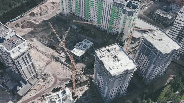 High cranes on construction site with skyscrapers. Construction of modern apartment buildings