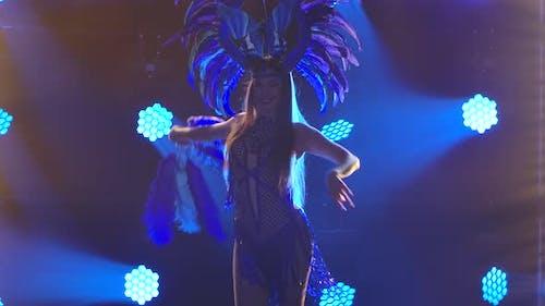 Une femme flamboyante dans un costume de carnaval, une coiffe haute et un fan de plumes danse