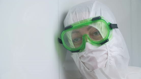 A doctor in protective clothing, a mask and goggles, close-up. Tired look. Antivirus suit