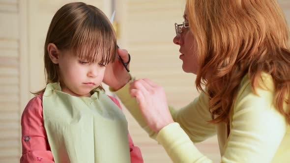 Thumbnail for Mama schneidet das Haar des Kindes