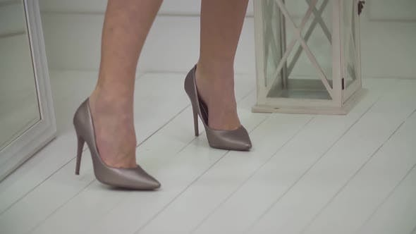 Female Legs in a Shoe with a Weighty Heel