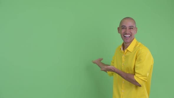 Thumbnail for Happy Handsome Bald Businessman Showing To Back and Looking Surprised