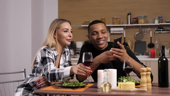 Gorgeous Interracial Couple Having Candle Light Dinner Looking at Phone Screen