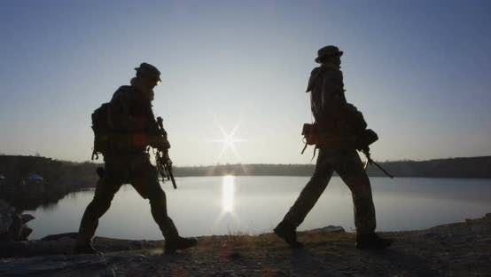 Soldiers Marching By a Lake at Sunset