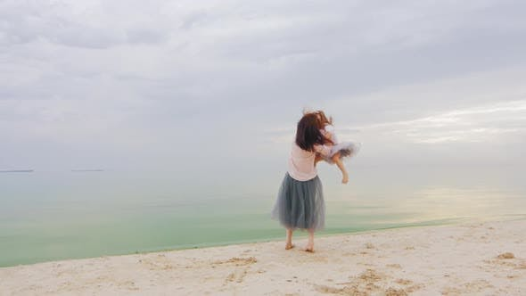Thumbnail for Carefree Young Mother Turns To the Hands of a Girl Playing with Her Against the Sea