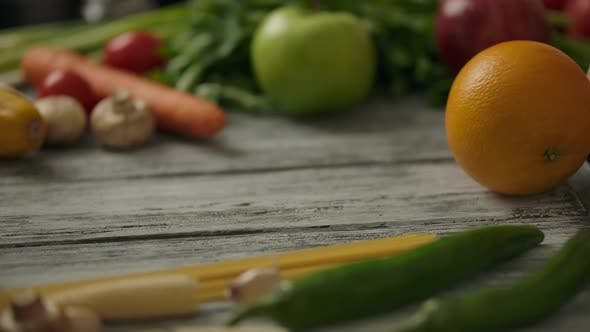 Thumbnail for Crop Person Rolling Orange on Wooden Rustic Table. Vegetarian Food Concept.