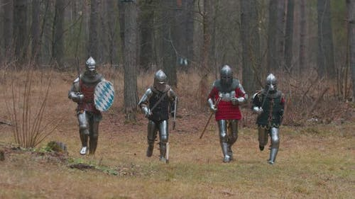Four Men Knightes Running in the Row in the Forest in Full Armour Holding Weapons