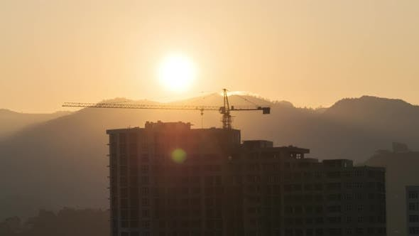 Thumbnail for Sunrise Over a Tower Crane on Construction Site with a Skyscraper in the City. Timelapse.
