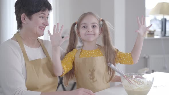 Thumbnail for Cute Little Girl Grimacing at Camera at Kitchen As Grandmother Laughing. Caucasian Child in Apron