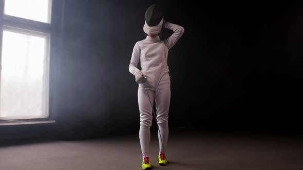 Cover Image for A Young Woman Fencer Walking To the Fighting Area and Stands in the Position