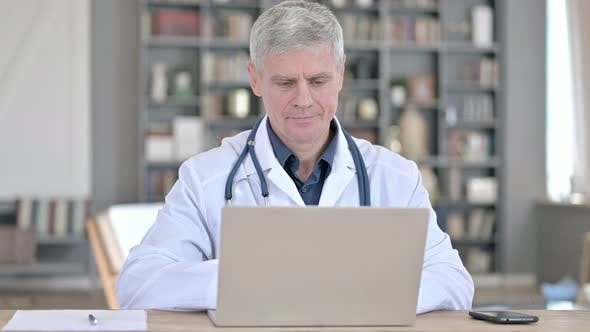 Professional Senior Doctor Working on Laptop While Sitting in Office