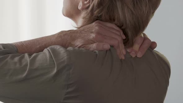 Cover Image for Elderly Woman Massaging Her Neck and Shoulders, Feeling Pain and Discomfort