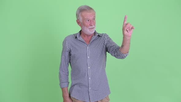 Thumbnail for Happy Senior Bearded Man Presenting and Touching Something
