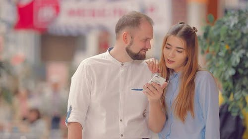 Couple in Mall Selects Item in Phone App