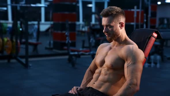 Strong handsome fitness trainer sits on sport chair and rests after training muscles.