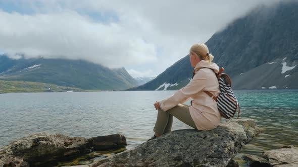 Thumbnail for A Female Traveler Sits on a Big Rock Admiring the Majestic Mountain Lakes in Norway