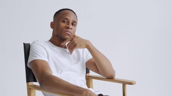 Dreamy Athletic Relaxed Black Young Man Sitting on a Armchair Against White Wall Backgroun