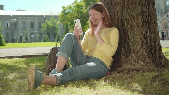 Cheerful Redhead Girl Using Video Chat Outdoors on Sunny Summer Day. Portrait of Positive Young
