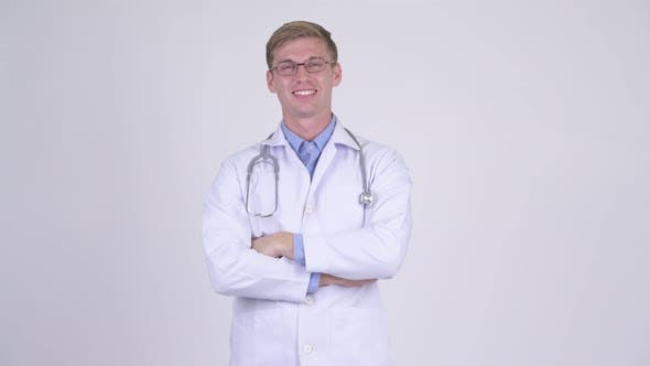 Thumbnail for Happy Young Handsome Man Doctor Wearing Eyeglasses with Arms Crossed