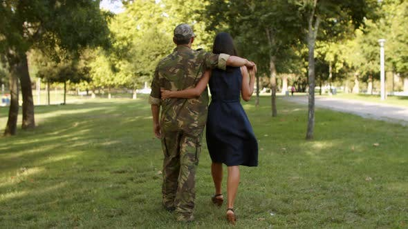 Military Man in Camouflage Uniform Embracing Girlfriend or Wife