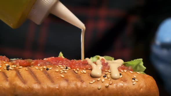 Prepares a Hot Dog