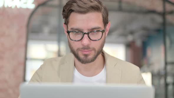 Close Up of Young Man with Laptop Looking at Camera