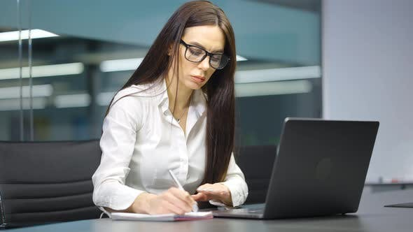 Businesswoman Writing Schedule for Meeting in Office