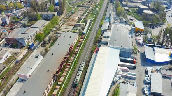 Thumbnail for The Train Moves By Rail Along an Industrial Area with Buildings and Warehouses