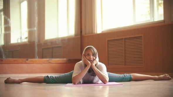 Young Pretty Woman Sitting on the Yoga Mat Performing a Split - Props Up the Face with Her Hands and
