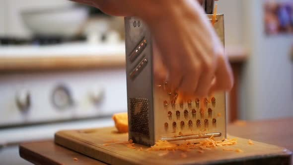 Thumbnail for Woman Hands Rubbing Carrots on Grater in a Home Kitchen. Slow Motion