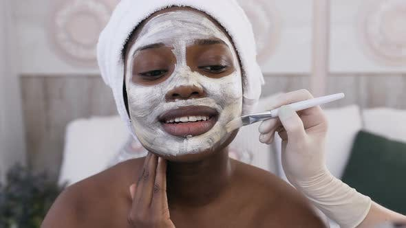 Thumbnail for African American Woman with Towel on the Head while Cosmetologist Hand Applying Mask on Her Face