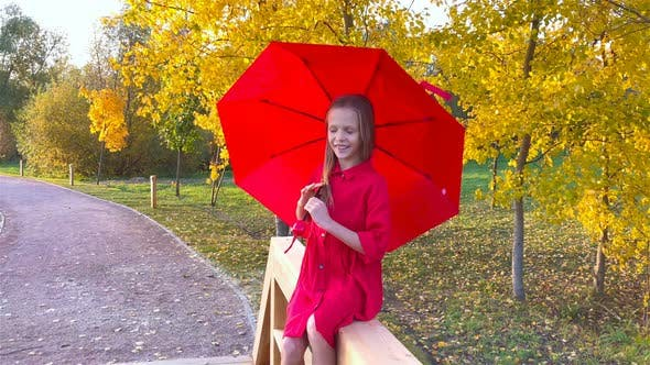 Thumbnail for Happy Child Girl Laughs Under Red Umbrella