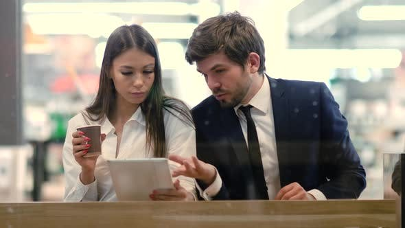 Thumbnail for Business Man and Woman Sitting Using Tablet in a Mall