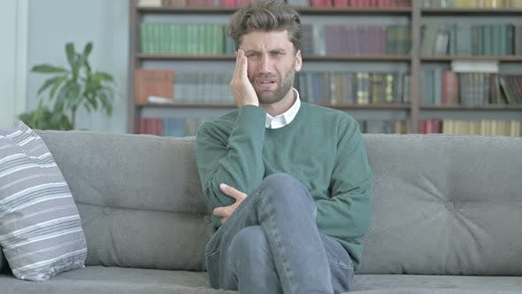 Cover Image for Depressed Young Man Having Headache and Massaging His Head