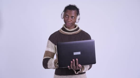 Thumbnail for Young Happy African Man Thinking While Using Laptop Ready for Winter