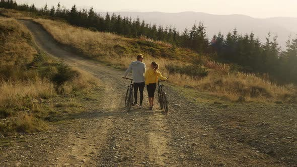 Guy and Girl Having Walk with Bicycles