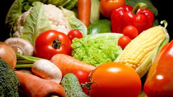 Nahaufnahme Video von viel frischem Gemüse der Saison vor schwarzem Hintergrund. Konzept des Gesundes