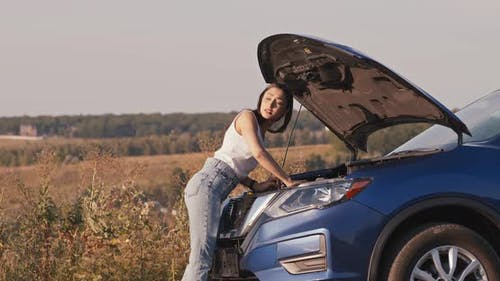 Young Woman Looking at Open Hood of Broken Car, Then Trying To Catch Vehicle for Help