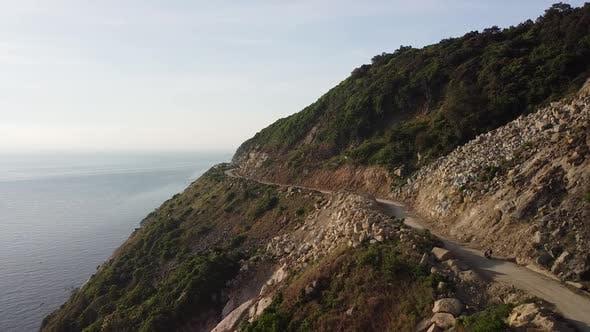 Thumbnail for Aerial View of Motorist Driving Motorbike on Dangerous Coastal Cliffside Road