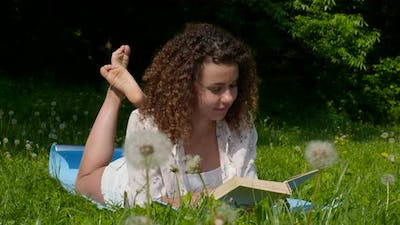 Student Girl Reads a Book on the Lawn in the Park
