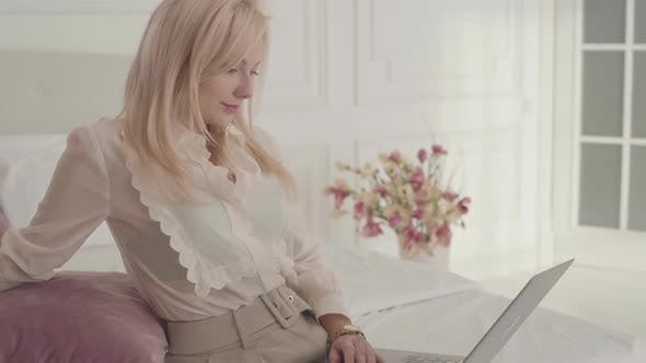 Thumbnail for Smiling Blond Caucasian Businesswoman Typing on the Laptop Sitting on the Bed at Home