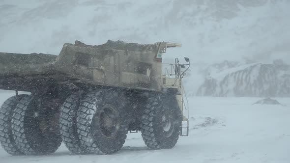 A Dumper Truck Drives Through an Open-pit Coal Mine in Winter