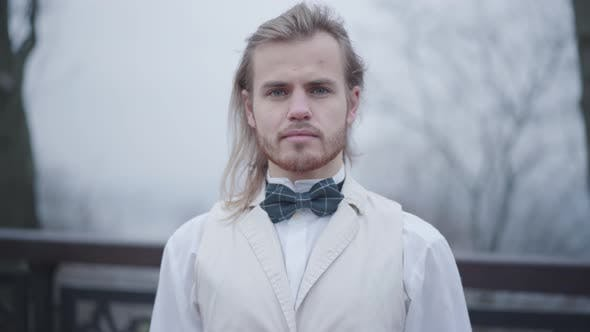Portrait of Young Confident Caucasian Man with Long Hair and Blue Eyes Dressed in White Shirt