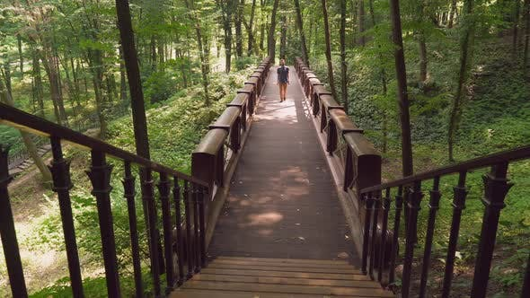 Thumbnail for A Young Male Walks on a Bridge in the Park and Goes Upstairs