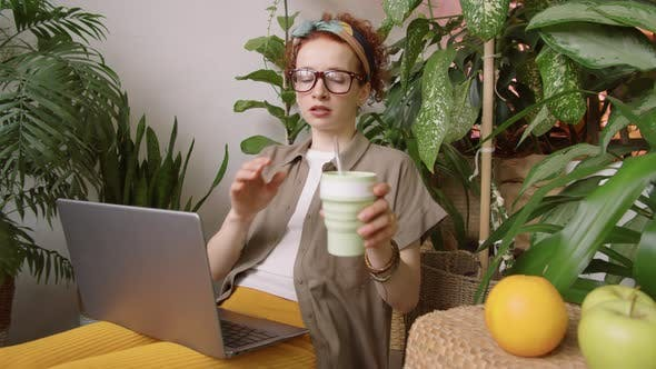 Pretty Woman Drinking from Eco-Friendly Cup and Typing on Laptop at Home