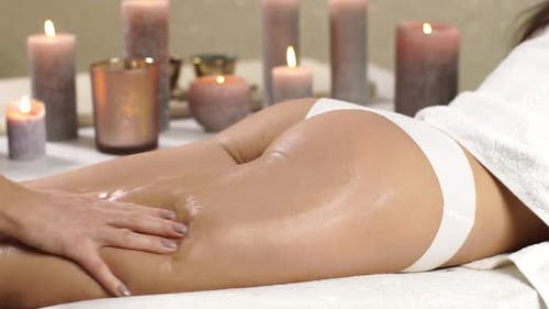 Spa Therapist Massaging Female Legs and Ass with Oil