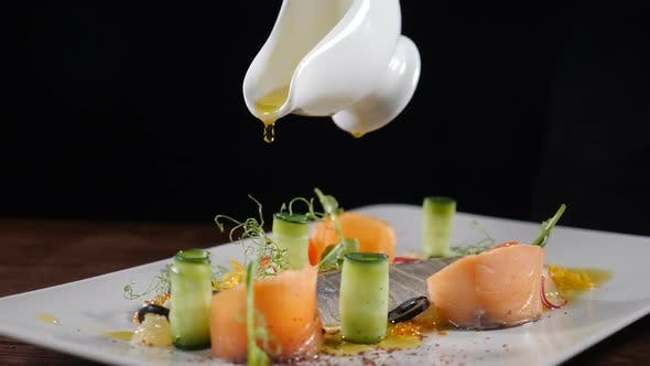 Thumbnail for Chef Pouring Extra Virgin Olive Oil Out of Sauce Boat on Herring Served with Cucumbers, Tamatoes and