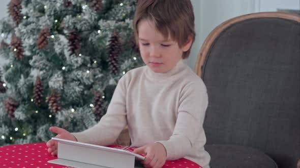 Thumbnail for Serious Little Boy Sitting on a Chair and Using Tablet During Christmas Time