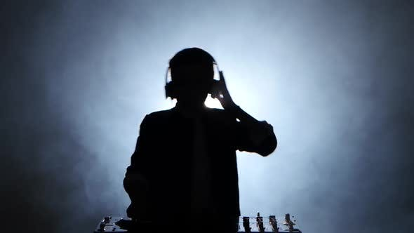 Thumbnail for Silhouette Boy Dj in Headphones Playing on Vinyl. Smoky Background