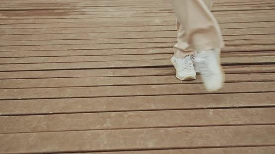 Woman Dancing In Sneakers On Seaside Pier